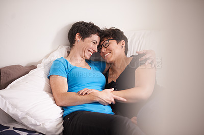 Buy stock photo Shot of an affectionate couple relaxing cuddling on the bed at home