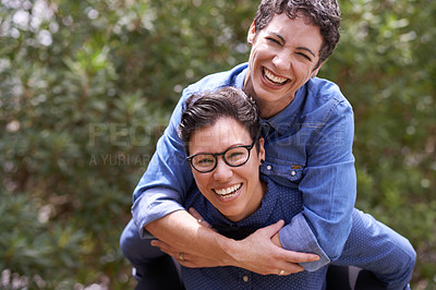 Buy stock photo Portrait of a happy couple enjoying a piggyback ride outside