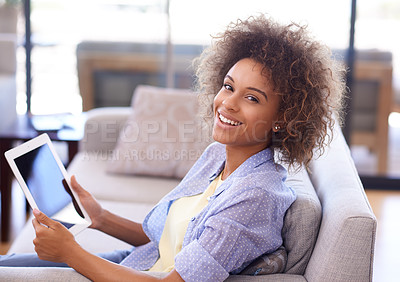 Buy stock photo Shot of a young woman using her tablet while relaxing on the sofa at home