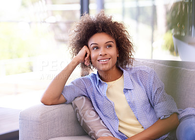 Buy stock photo Shot of a young woman looking thoughtful while sitting on her living room sofa