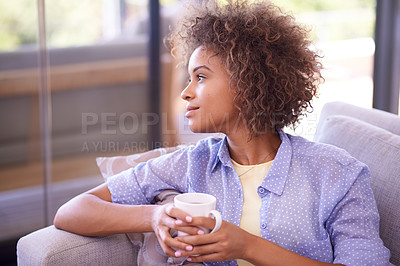 Buy stock photo Shot of a young woman having coffee while relaxing on her living room sofa