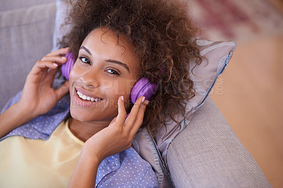 Buy stock photo Shot of a woman listening to music through her headphones while lying on her sofa