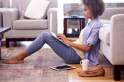 Buy stock photo Shot of a woman using her laptop while sitting on her living room floor