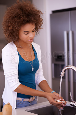 Buy stock photo Shot of a young woman washing her hands in the kitchen sink