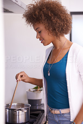Buy stock photo Shot of a young woman cooking a meal in her kitchen