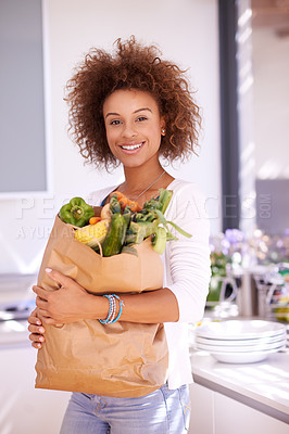 Buy stock photo Portrait of a young woman holding a bag of groceries