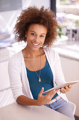 Buy stock photo Shot of a young woman using her tablet at home