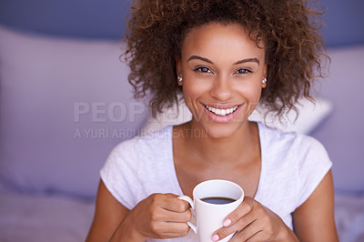 Buy stock photo Shot of a young woman enjoying a beverage on her bed in the morning