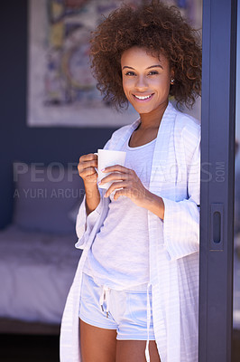 Buy stock photo Shot of a young woman enjoying a beverage in the morning