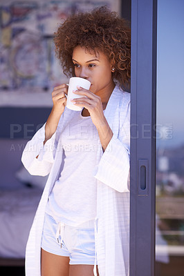 Buy stock photo Shot of a thoughtful young woman drinking a beverage in the morning