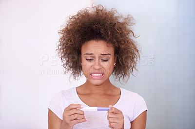 Buy stock photo Shot of a young woman looking at the results on her pregnancy test