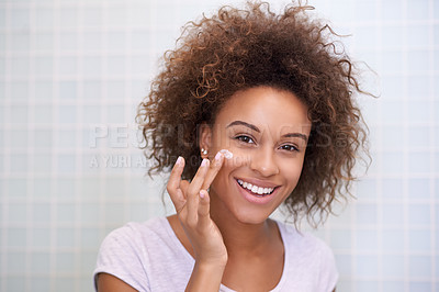 Buy stock photo Portrait of a young woman moisturizing her face
