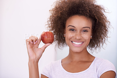 Buy stock photo Portrait of a beautiful young woman holding an apple isolated on white