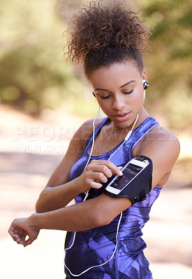 Buy stock photo Shot of an attractive young woman checking her playlist before a run