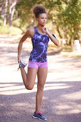 Buy stock photo Shot of an attractive young woman stretching before her run