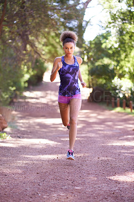 Buy stock photo Shot of an attractive young woman jogging in the forest