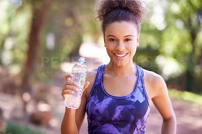 Buy stock photo Shot of a sporty young woman drinking water after her workout
