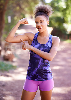 Buy stock photo Shot of a sporty young woman flexing her muscles