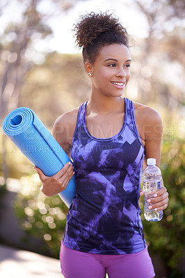 Buy stock photo Shot of a young woman in exercise clothes holding a yoga mat while standing outdoors