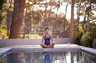 Buy stock photo Shot of an attractive young woman doing yoga outdoors