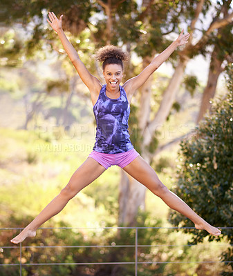 Buy stock photo Shot of an attractive young woman in exercise clothes jumping outdoors