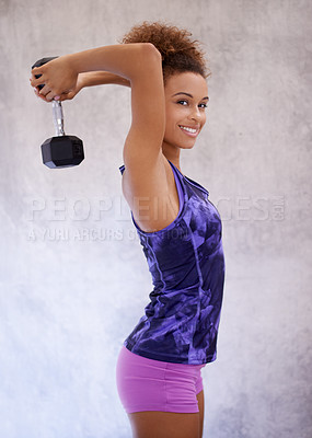 Buy stock photo Portrait of an attractive young woman lifting dumbells while standing outside