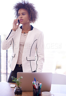 Buy stock photo Shot of a young businesswoman talking on her phone in an office