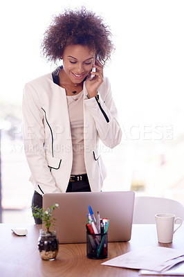Buy stock photo Shot of a young businesswoman talking on her phone and using a laptop in an office
