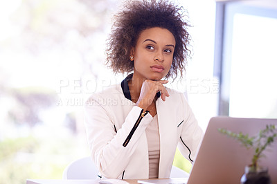 Buy stock photo Shot of a thoughtful young businesswoman using a laptop in an office