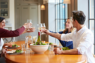 Buy stock photo Shot of a group of friends toasting together over dinner