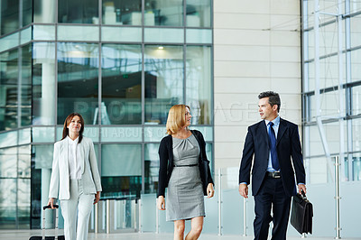 Buy stock photo Shot of businesspeople walking through the lobby of an office building