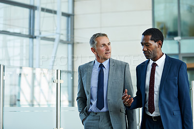 Buy stock photo Shot of two businessmen walking and talking together in the lobby of an office building