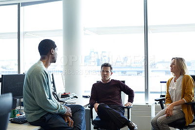 Buy stock photo Shot of a group of casually dressed businesspeople talking in the office