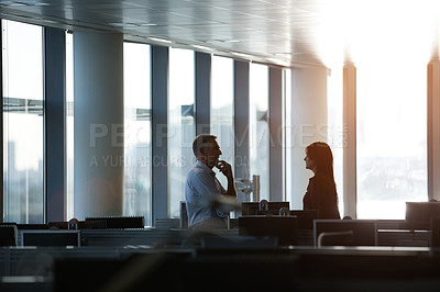 Buy stock photo Shot of two businesspeople talking together in the office late in the afternoon