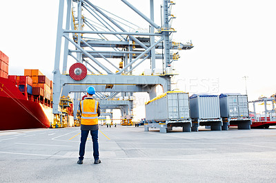 Buy stock photo Rearview shot of a man in workwear looking up at a crane on a commercial dock