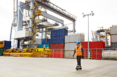 Buy stock photo Shot of a young man in workwear walking outside on a large commercial dock