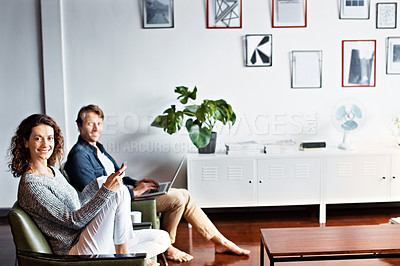 Buy stock photo Shot of a content mature couple sitting in their living room using a cellphone and using a laptop