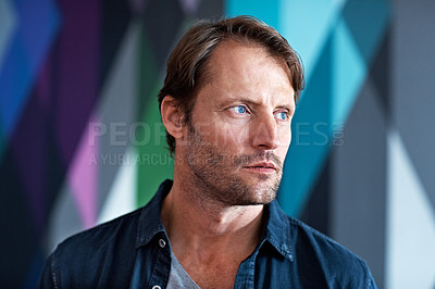 Buy stock photo Shot of a serious looking man standing in front of a colorful background