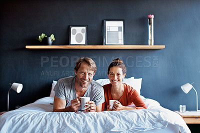 Buy stock photo Portrait of a smiling mature couple lying on their bed drinking coffee