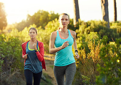 Buy stock photo Shot of two young woman out for a cross country run