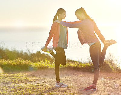 Buy stock photo Shot of two young friends stretching before a trail run