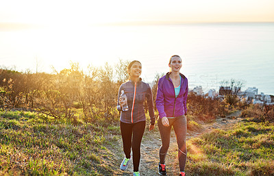 Buy stock photo Shot of two friends talking together while out for a cross country walk