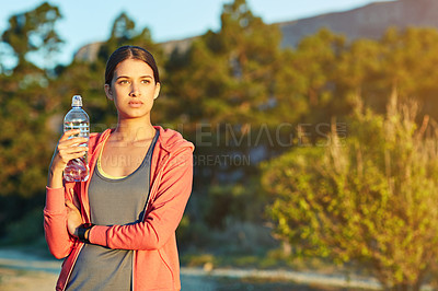 Buy stock photo Portrait of a young woman taking a water break while out for a cross country run