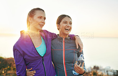 Buy stock photo Shot of two smiling young friends standing arm in arm while out for a run