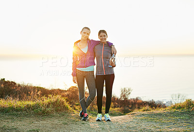 Buy stock photo Portrait of two smiling young friends standing arm in arm while out for a run