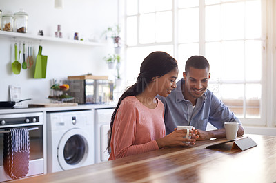 Buy stock photo Shot of a young couple drinking coffee and using their tablet in the kitchen