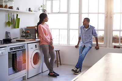 Buy stock photo Shot of a young couple talking in the kitchen