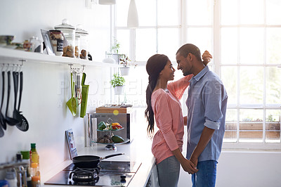 Buy stock photo Shot of an affectionate young couple hugging in the kitchen