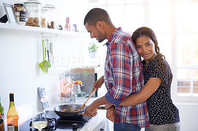 Buy stock photo Shot of an affectionate young couple preparing dinner in their kitchen