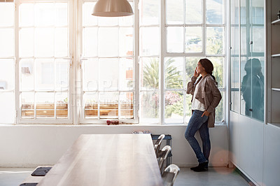 Buy stock photo Shot of a young woman standing in her kitchen talking on the phone